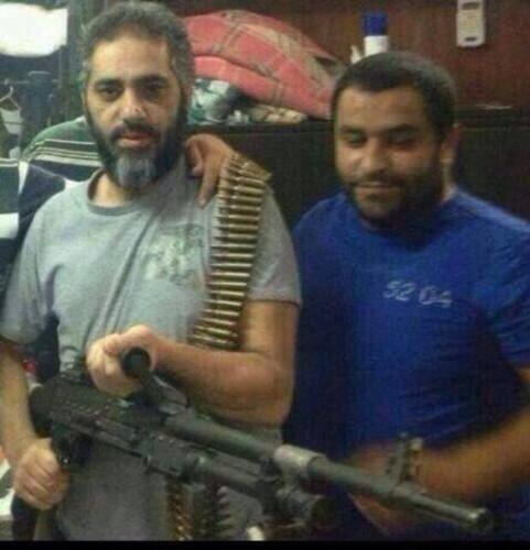 Fadel Shaker holding a gun